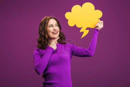 Photo pour Femme souriante pointant du doigt à la bulle de pensée sur fond violet - image libre de droit