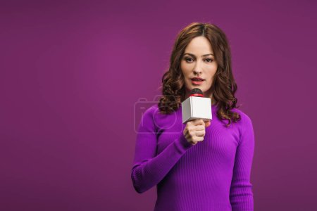 Photo for Attractive reporter talking in microphone on purple background - Royalty Free Image
