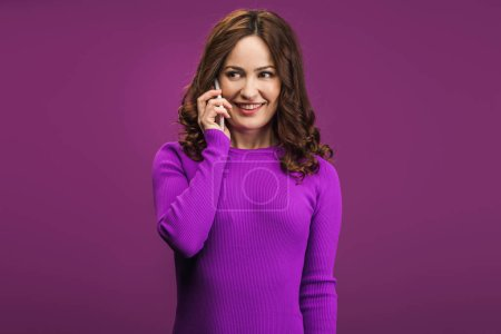 Photo for Smiling woman talking on smartphone on purple background - Royalty Free Image