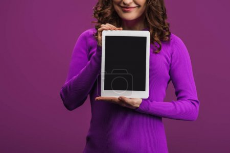 cropped view of smiling woman holding digital tablet with blank screen on purple background