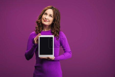 Photo pour Femme souriante tenant tablette numérique avec écran blanc sur fond violet - image libre de droit