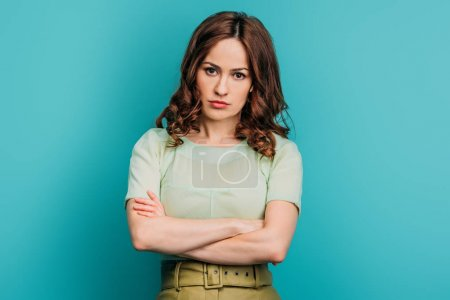 Photo for Serious woman looking at camera while standing with crossed arms on blue background - Royalty Free Image