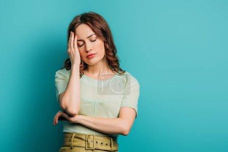 Photo pour Femme épuisée touchant la tête tout en se tenant les yeux fermés sur fond bleu - image libre de droit