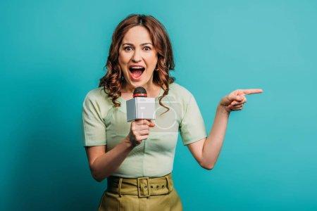 Photo pour Journaliste excité pointant du doigt tout en tenant le microphone sur fond bleu - image libre de droit