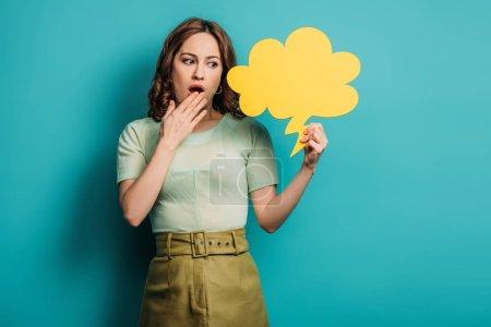Photo pour Femme choquée tenant la main près de la bouche tout en tenant bulle de pensée sur fond bleu - image libre de droit