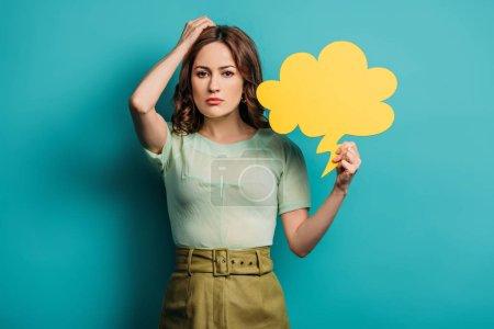 Photo pour Une femme réfléchie se touchant la tête en tenant une bulle sur fond bleu - image libre de droit