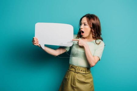 Photo for Shocked woman pointing with finger at speech bubble on blue background - Royalty Free Image