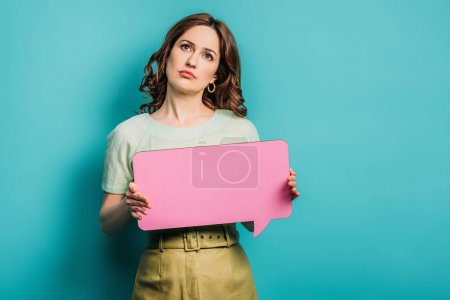 Photo for Thoughtful woman looking up while holding speech bubble on blue background - Royalty Free Image