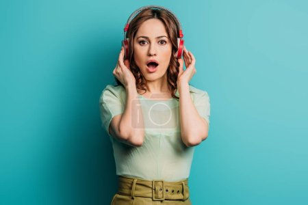 Photo for Surprised girl in wireless headphones looking at camera blue background - Royalty Free Image