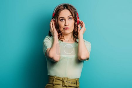 skeptical girl in wireless headphones looking up on blue background