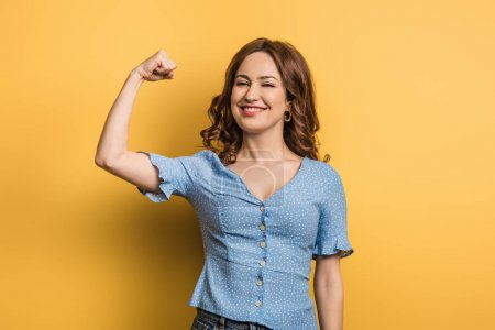 cheerful woman showing power while looking at camera on yellow background