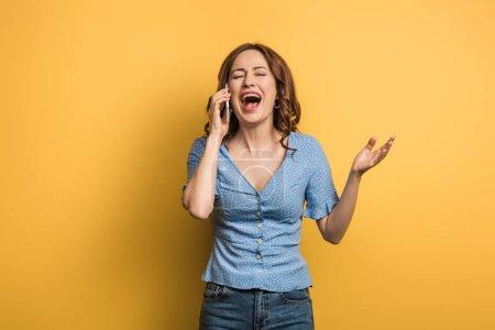 Photo pour Femme gaie riant avec les yeux fermés tout en parlant sur smartphone sur fond jaune - image libre de droit