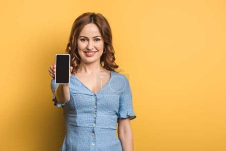 smiling girl looking at camera while showing smartphone with blank screen on yellow background