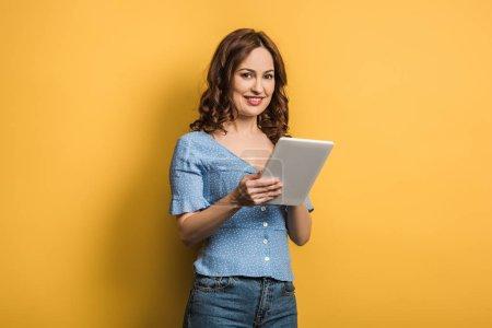 Photo pour Jeune femme souriant à la caméra tout en utilisant une tablette numérique sur fond jaune - image libre de droit