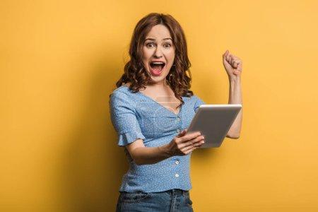 Foto de Mujer emocionada que muestra gesto de ganador mientras mantiene la tableta digital sobre fondo amarillo. - Imagen libre de derechos
