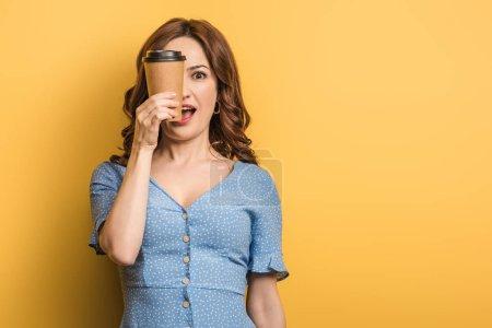 Photo pour Femme joyeuse couvrant les yeux avec une tasse de papier sur fond jaune - image libre de droit