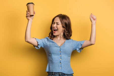 Photo for Excited girl showing winner gesture while holding paper cup on yellow background - Royalty Free Image