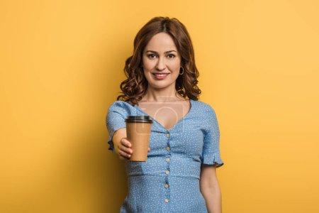 Photo pour Gaie fille tenant café pour aller tout en regardant la caméra sur fond jaune - image libre de droit