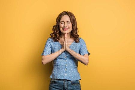 Photo pour Fille anxieuse montrant les mains priantes avec les yeux fermés sur fond jaune - image libre de droit