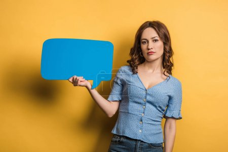 offended girl looking at camera while holding speech bubble on yellow background