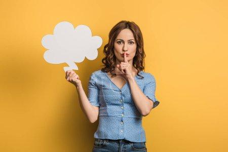 Photo pour Une jeune femme positive montrant un signe de brousse alors qu'elle tient une bulle d'air sur fond jaune - image libre de droit