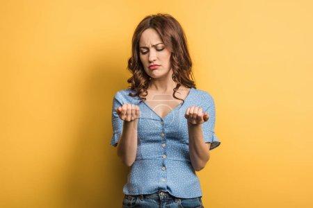 Photo pour Une jeune femme dérangée regardant la manucure sur fond jaune - image libre de droit