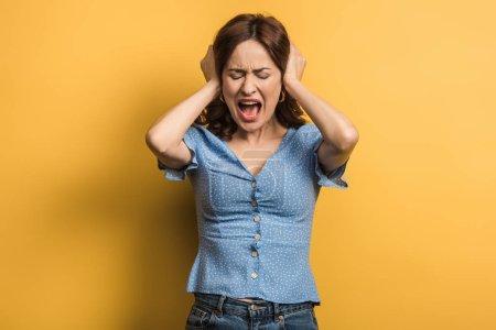 Photo pour Fillette en colère criant en se couvrant les oreilles avec les mains sur fond jaune - image libre de droit
