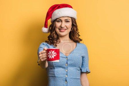 Photo pour Happy girl en santa chapeau tenant une tasse de boisson chaude sur fond jaune - image libre de droit