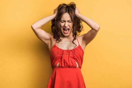 Photo pour Jeune femme en colère criant tout en se tenant les yeux fermés et touchant les cheveux sur fond jaune - image libre de droit