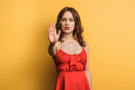 Foto de Seria mujer joven mirando la cámara y mostrando el gesto de parada en el fondo amarillo - Imagen libre de derechos