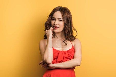 Foto de Una jovencita soñadora que tiene la mano cerca de la cara y mira la cámara en el fondo amarillo. - Imagen libre de derechos