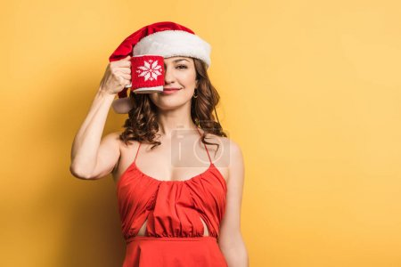 cheerful girl in santa hat covering eye with cup on yellow background