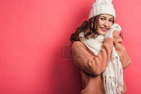 Photo pour Froid, fille souriante en chapeau chaud et écharpe debout avec les mains serrées sur fond rose - image libre de droit