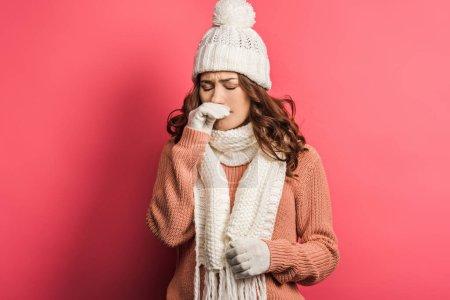 Photo pour Fille malade en chapeau chaud et écharpe toucher le nez sur fond rose - image libre de droit