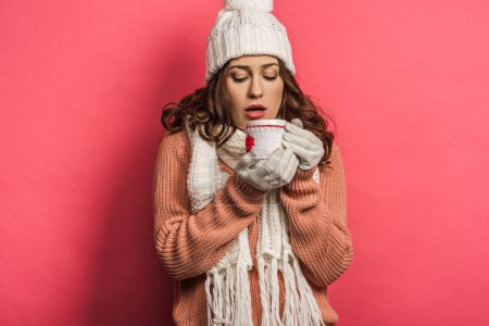 Foto de Niña fría en sombrero caliente y copa de pañuelo con bebida caliente en fondo rosa. - Imagen libre de derechos