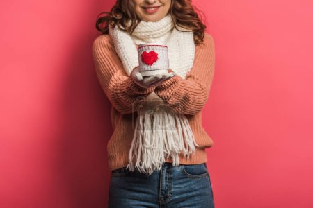Photo for Cropped view of smiling girl in warm scarf holding cup with heart symbol on pink background - Royalty Free Image