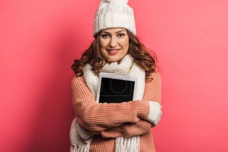 Photo pour Fille souriante en chapeau chaud et écharpe tenant tablette numérique sur fond rose - image libre de droit