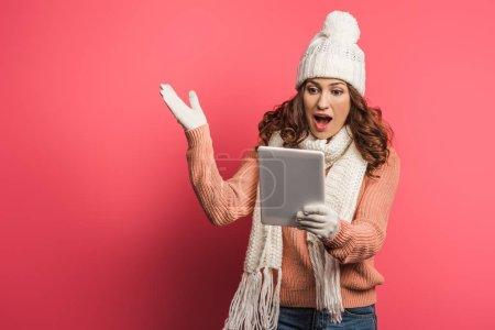 Photo pour Fille surprise en chapeau chaud et écharpe regardant tablette numérique sur fond rose - image libre de droit