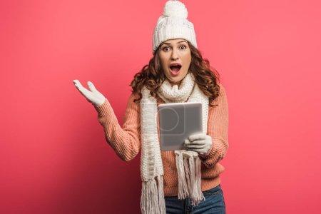 Photo pour Fille choquée en chapeau chaud et écharpe tenant tablette numérique sur fond rose - image libre de droit