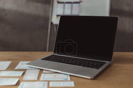 Photo pour Mise au point sélective de l'ordinateur portatif avec écran vierge et cadre filaire du site Web sur la table - image libre de droit