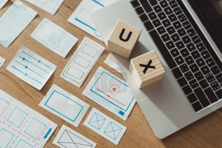 Photo for High angle view of cubes with ux letters on laptop with website wireframe sketches on wooden table - Royalty Free Image