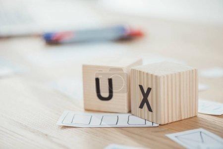 Photo pour Concentration sélective de cubes en bois avec lettres ux et croquis sur table - image libre de droit
