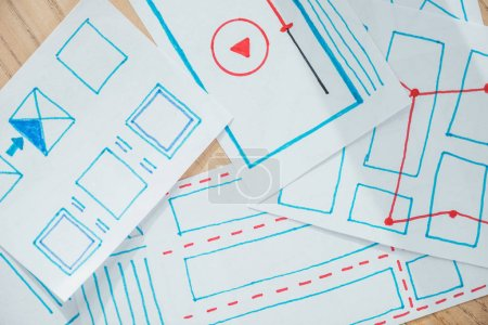 Photo for Top view of ux sketch layouts on wooden table - Royalty Free Image