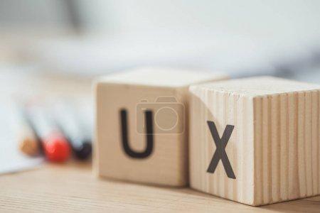 Photo pour Concentration sélective de cubes en bois avec des lettres ux sur la table - image libre de droit