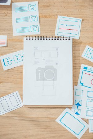 Photo for Top view of ux website wireframe sketches and planning applications on wooden table - Royalty Free Image
