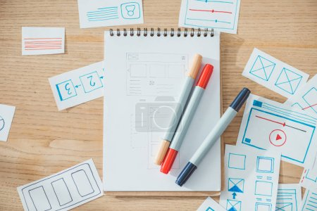 Photo for Top view of pens on notebook with website ux app sketches on wooden table - Royalty Free Image