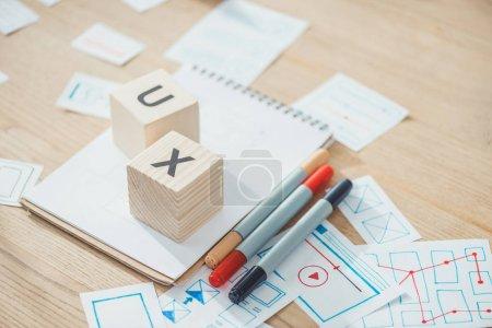 Foto de Enfoque selectivo de las letras ux en cubos con desarrollo de aplicaciones web bocetos en tablas de madera. - Imagen libre de derechos
