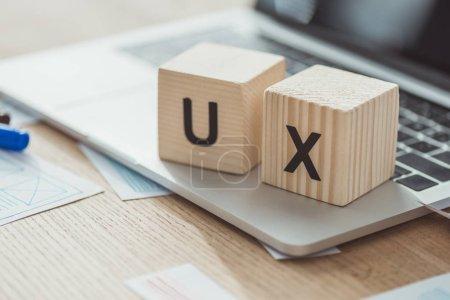 Photo pour Focalisation sélective des lettres ux sur les cubes sur ordinateur portable avec des esquisses web sur la table - image libre de droit