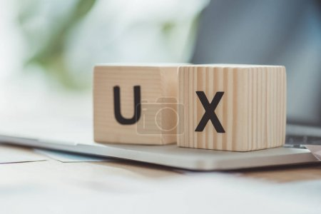 Photo for Selective focus of wooden cubes with ux letters on laptop on table - Royalty Free Image