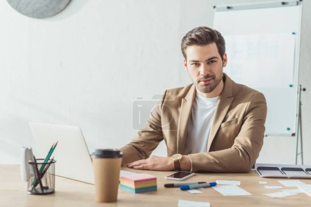 Handsome designer looking at camera while working with laptop and ux website templates in office